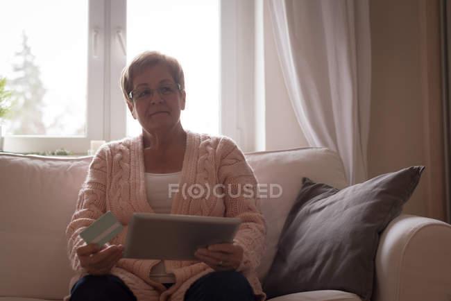 Seniorin beim Online-Einkauf auf digitalem Tablet zu Hause — Stockfoto
