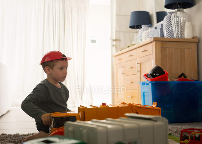 Boy playing with toys in living room at home — Stock Photo