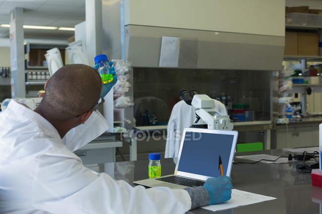 Wissenschaftler überprüft chemische Lösung im Labor — Stockfoto