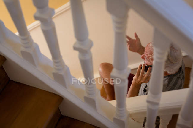 Senior man talking on mobile phone on stairs at home — Stock Photo