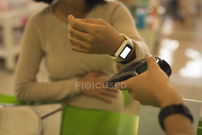 Pregnant woman making payment through smartwatch in store — Stock Photo