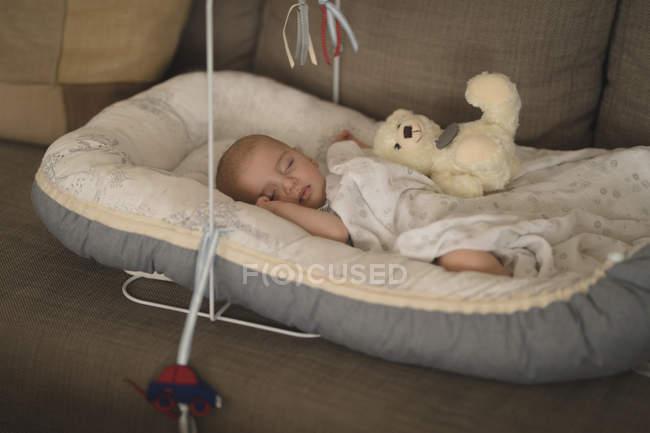 Милый маленький ребенок спит в кроватке на диване у себя дома — стоковое фото