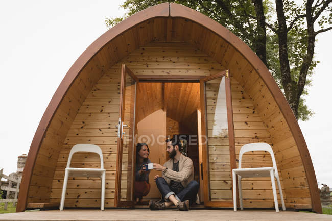 Счастливая пара, имея кофе на входе кабины журнала — стоковое фото
