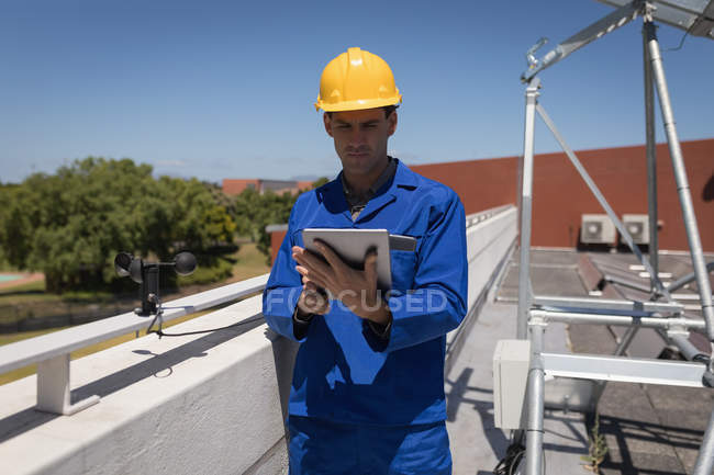 Male worker using digital tablet at solar station on a sunny day — Stock Photo