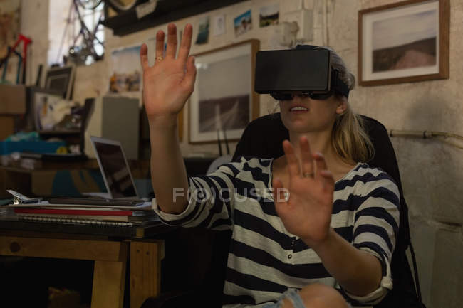 Young female mechanic using virtual reality headset in workshop — Stock Photo