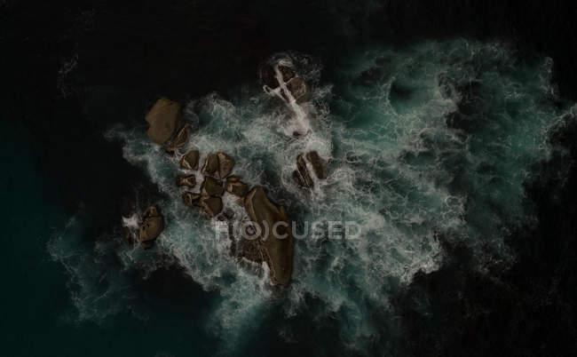 Вид с воздуха на скалистый остров в темной морской воде . — стоковое фото