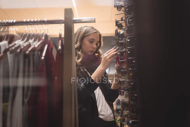 Hermosa chica seleccionando gafas de sol de la pantalla en el centro comercial - foto de stock