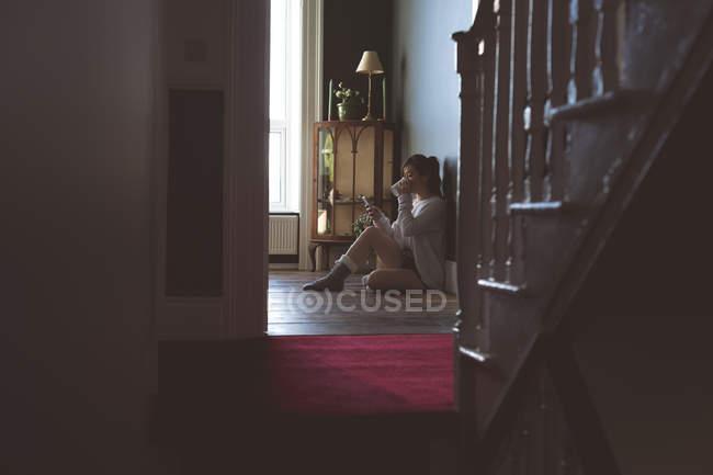 Woman having coffee while using mobile phone at home — Fotografia de Stock