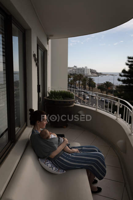 Young mom sitting on bench carrying her baby in sling at balcony on a sunny day — Stock Photo