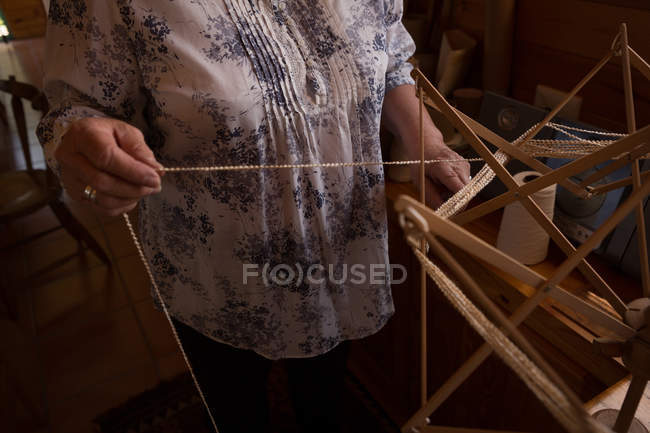 Mid section of woman using weaving loom at shop — Stock Photo