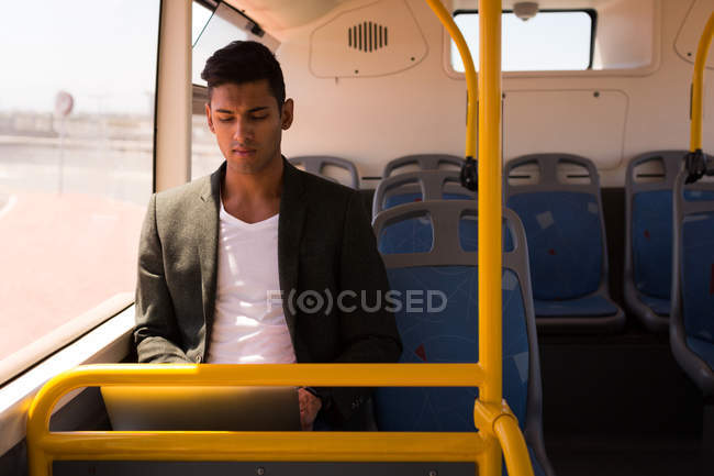 Young businessman using laptop while travelling in bus — Stock Photo