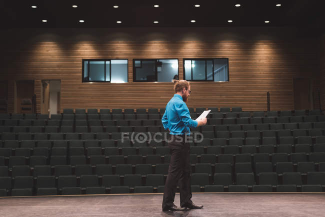 Male actor reading script on stage at theatre  — one person, casual