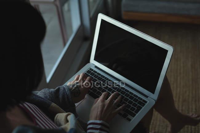 Primer plano de la mujer que usa el ordenador portátil en casa - foto de stock