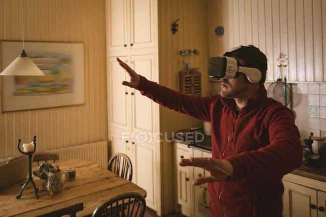 Homme utilisant casque de réalité virtuelle à la maison — Photo de stock