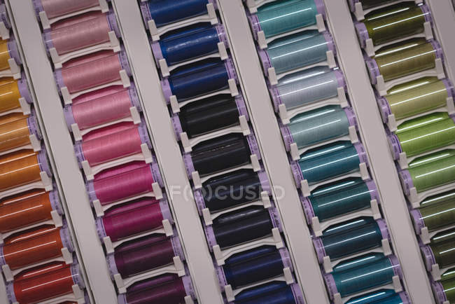 Multicolored threads arranged in row in tailor shop — Stock Photo