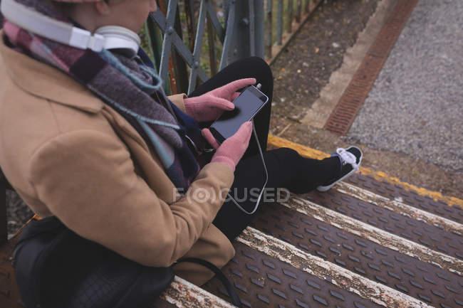 Belle femme assise sur les escaliers et utilisant un téléphone mobile — Photo de stock