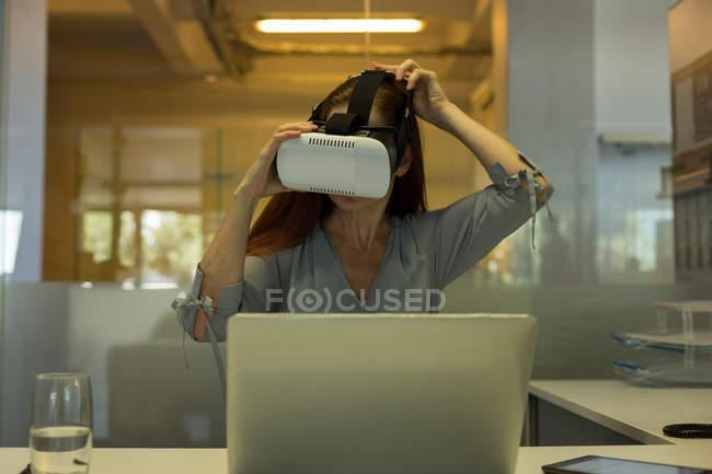 Ejecutiva con auriculares de realidad virtual en la oficina - foto de stock