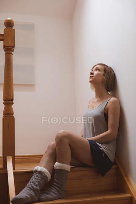 Вдумчивый красивая женщина, сидя на лестнице дома — стоковое фото