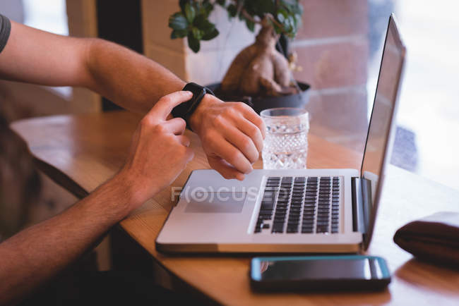 Close-up of man using smartwatch while sitting with laptop in cafe. — Stock Photo