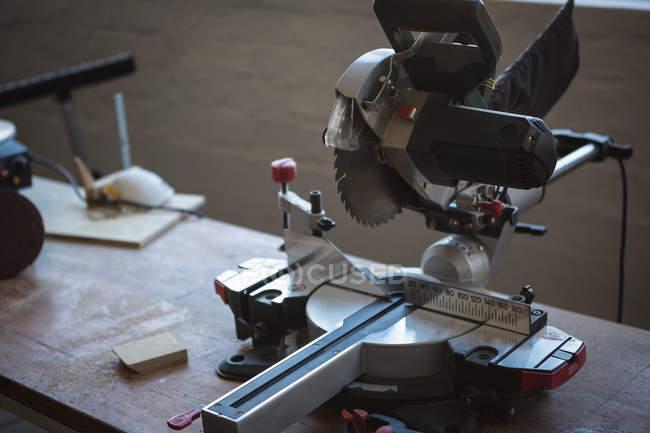 Primo piano della sega elettrica sulla tavola di legno in officina — Foto stock