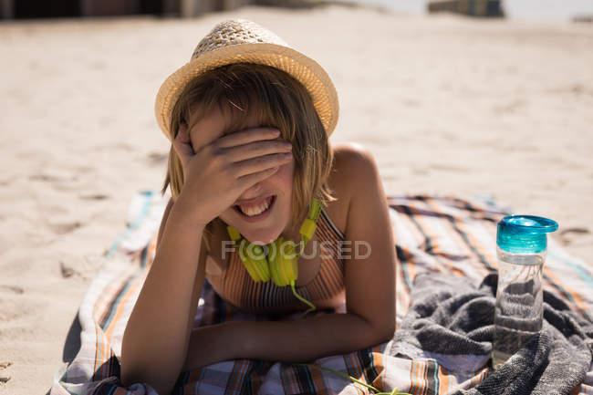 Дівчинка-підліток, що охоплюють її очі під час відпочинку на пляжі на сонячний день — стокове фото