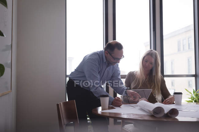 Business colleagues discussing over glass digital tablet in office — Stock Photo