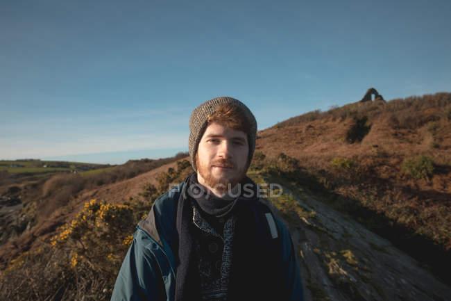 Ritratto di escursionista di sesso maschile rilassante e guardando in camera la campagna — Foto stock