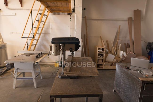 Vertical drilling machine on table in workshop interior. — Stock Photo