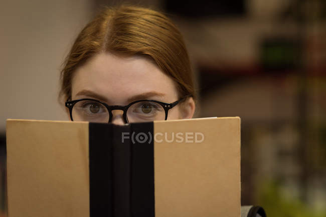 Close-up of woman with spectacles hiding face behind book in library — Stock Photo