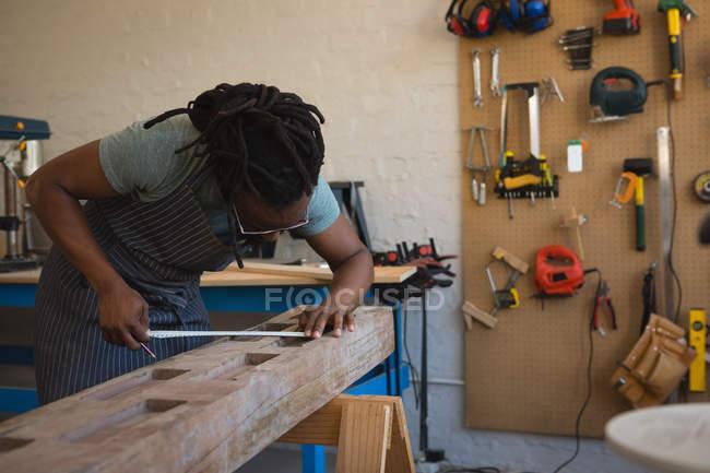 Tischler misst Holzplanke mit Maßband in Werkstatt — Stockfoto