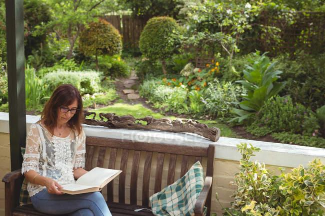 Женщина читает книгу на крыльце — стоковое фото