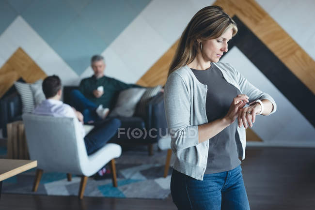 Businesswoman using smartwatch in office — Stock Photo
