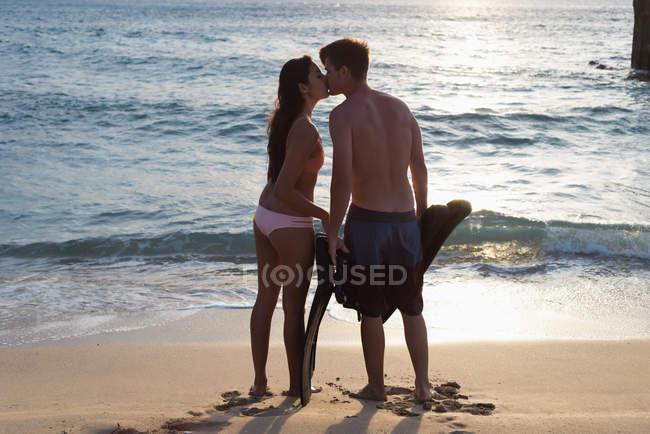 Романтическая пара целуется на песчаном пляже — стоковое фото