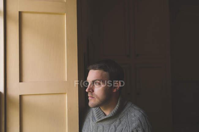 Вдумливий чоловік дивиться через вікно на дому — стокове фото