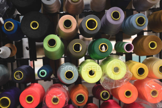 Close-up multicolored threads arranged in row in tailor shop — Stock Photo