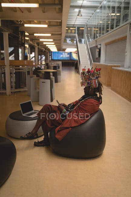 Maasai man in traditional clothing using mobile phone at shopping center — Stock Photo