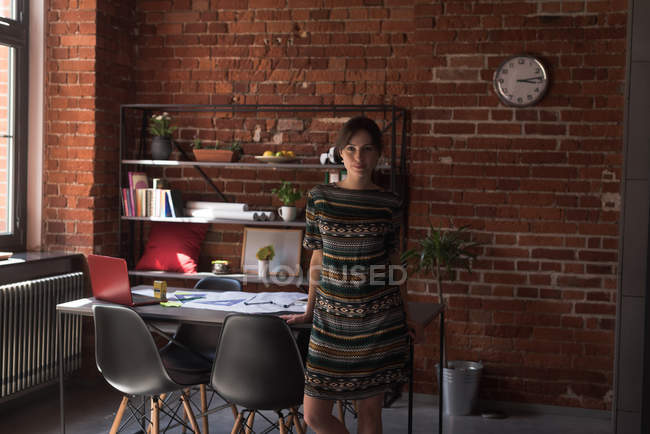 Young female executive standing in office — Stock Photo