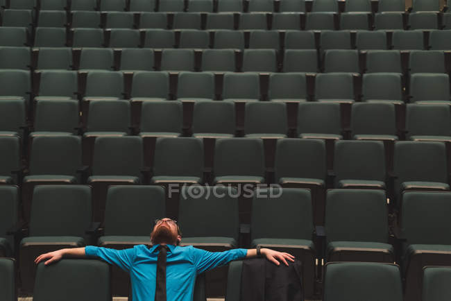 Thoughtful man relaxing and looking up on theater seats. — Stock Photo