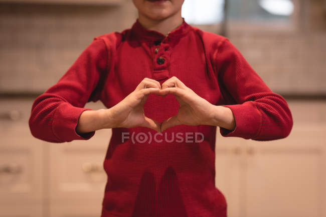 Garçon formant la forme du cœur avec les mains à la maison — Photo de stock