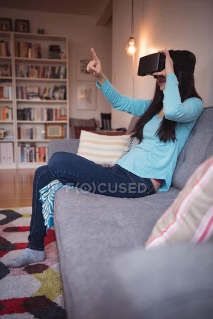 Mulher usando fone de ouvido realidade virtual na sala de estar em casa — Fotografia de Stock