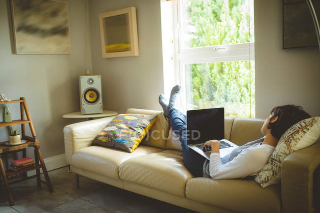Женщина с ноутбуком в гостиной на дому — стоковое фото