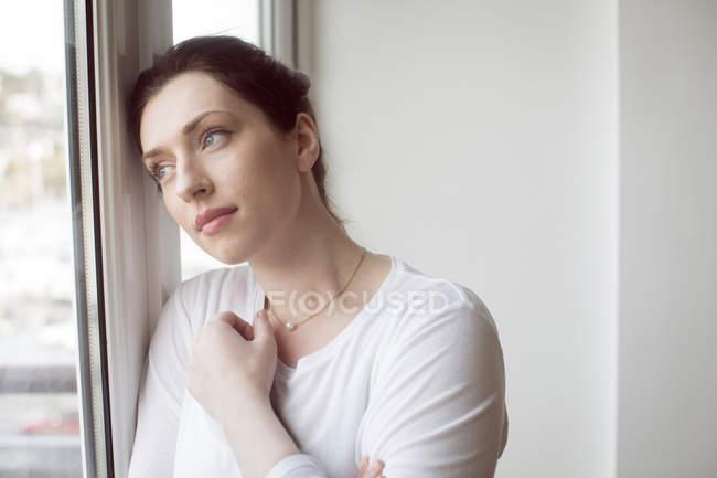 Продуманий жінка, стоячи біля вікна будинку. — стокове фото