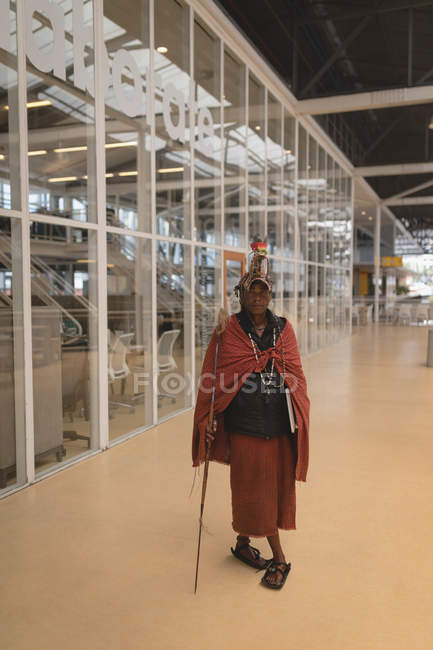 Porträt von Maasai Mann in traditioneller Kleidung stehend mit Stock in der Shopping mall — Stockfoto
