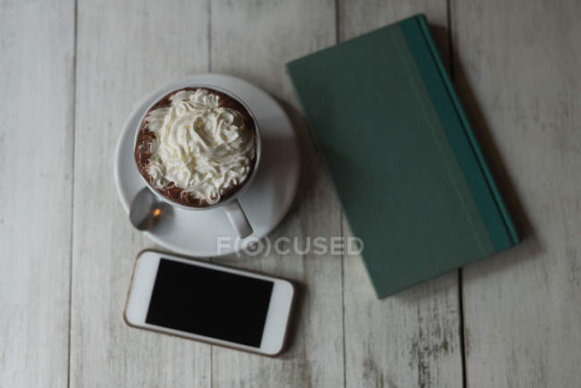 Sobrecarga de comida dulce, diario y teléfono móvil en mesa de madera - foto de stock