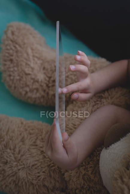 Recortar vista de niña con oso de peluche con tableta digital de vidrio en dormitorio - foto de stock