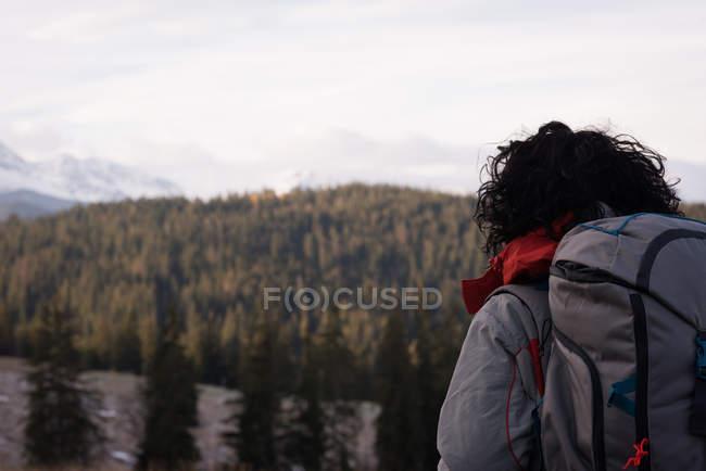 Vista trasera de la mujer de pie con mochila en el campo - foto de stock