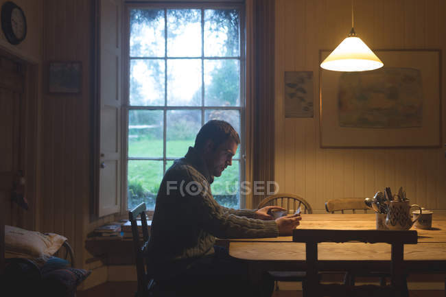 Man having coffee while using digital tablet at home — Stock Photo