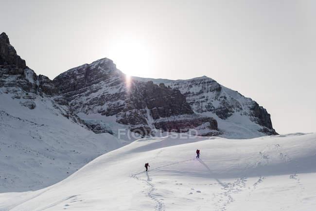 Paar läuft im Winter auf einem schneebedeckten Berg — Stockfoto