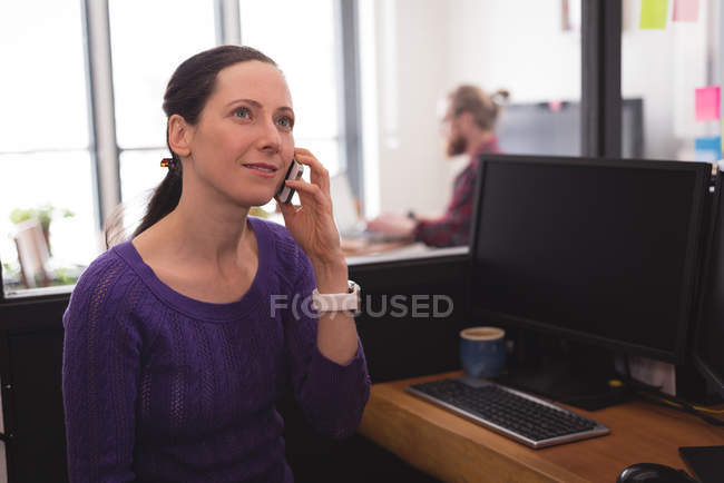 Female executive talking on mobile phone at desk in office — Stock Photo