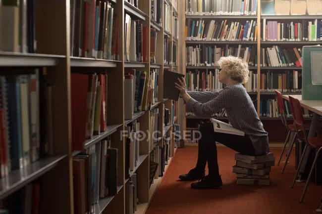 Молода жінка, видалення книги з полиці в бібліотеці — стокове фото